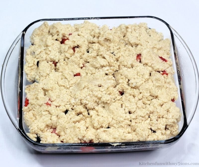 The dough crumble on top of the mixture of berries.
