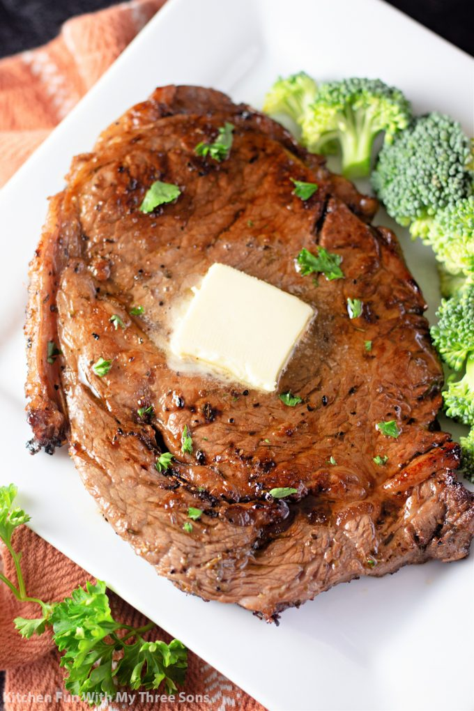 freshly made steak with butter and broccoli.