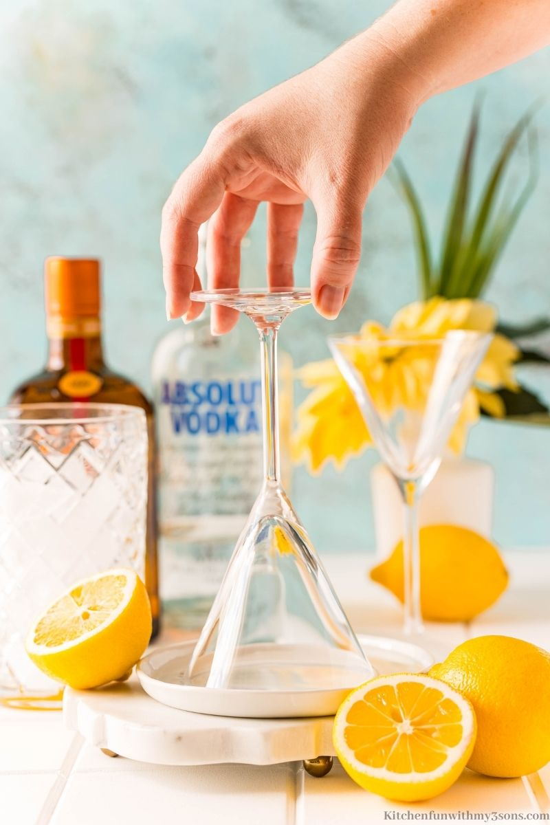 Dipping the martini glass in the syrup and sugar.