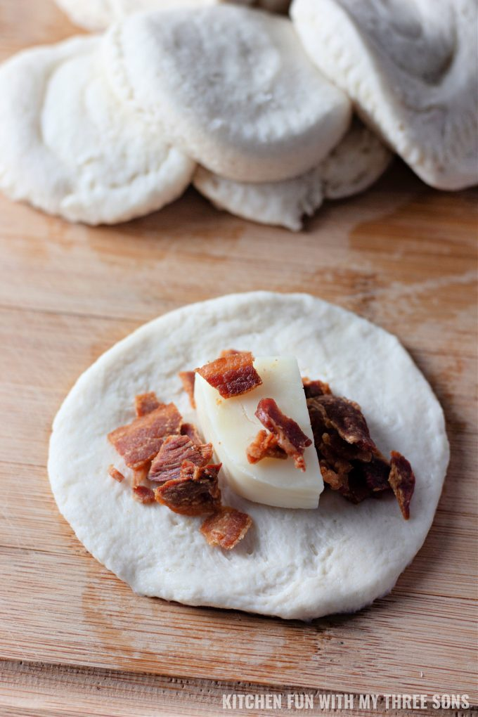topping circles of biscuit dough with cheese and bacon.