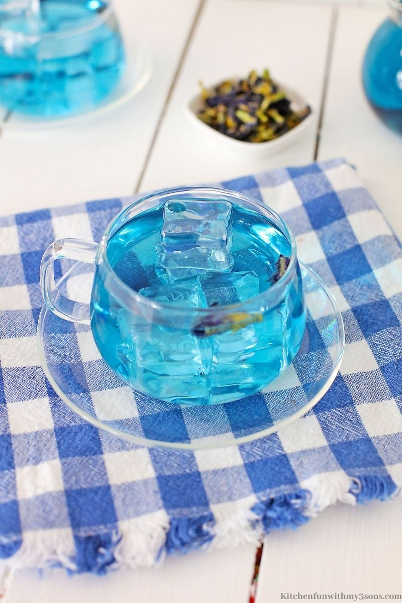 The cup of tea on a white and blue checkered cloth.