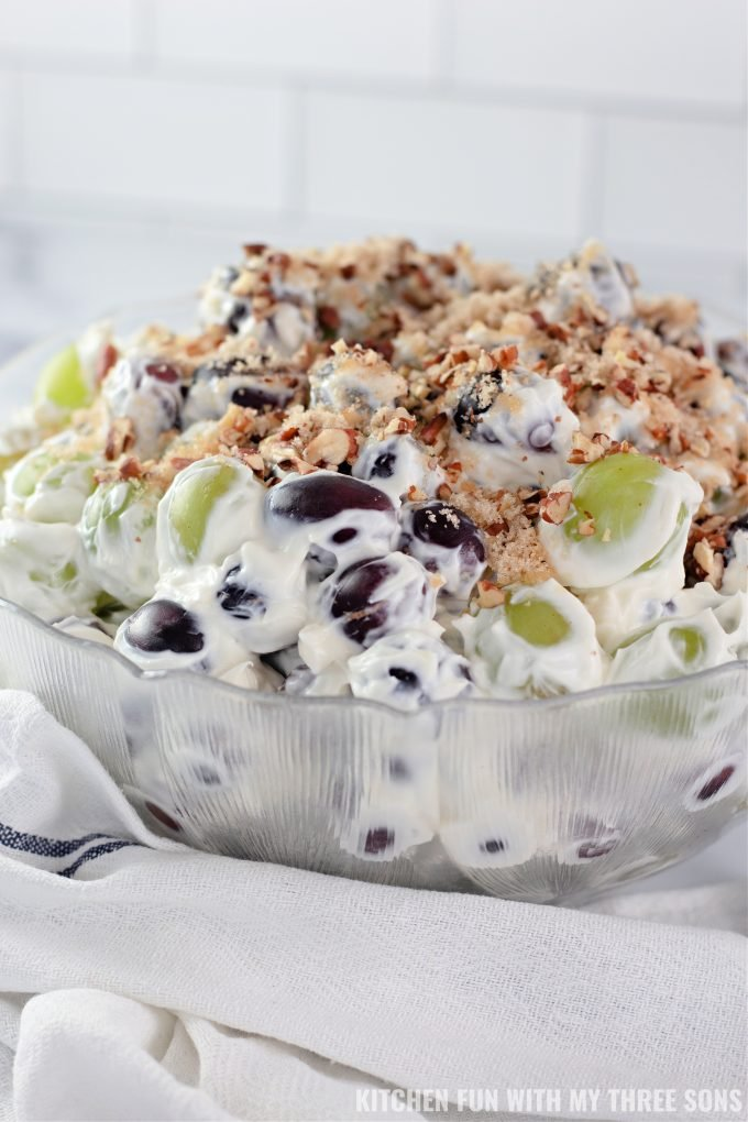 Creamy Grape Salad in a clear mixing bowl on a white counter.