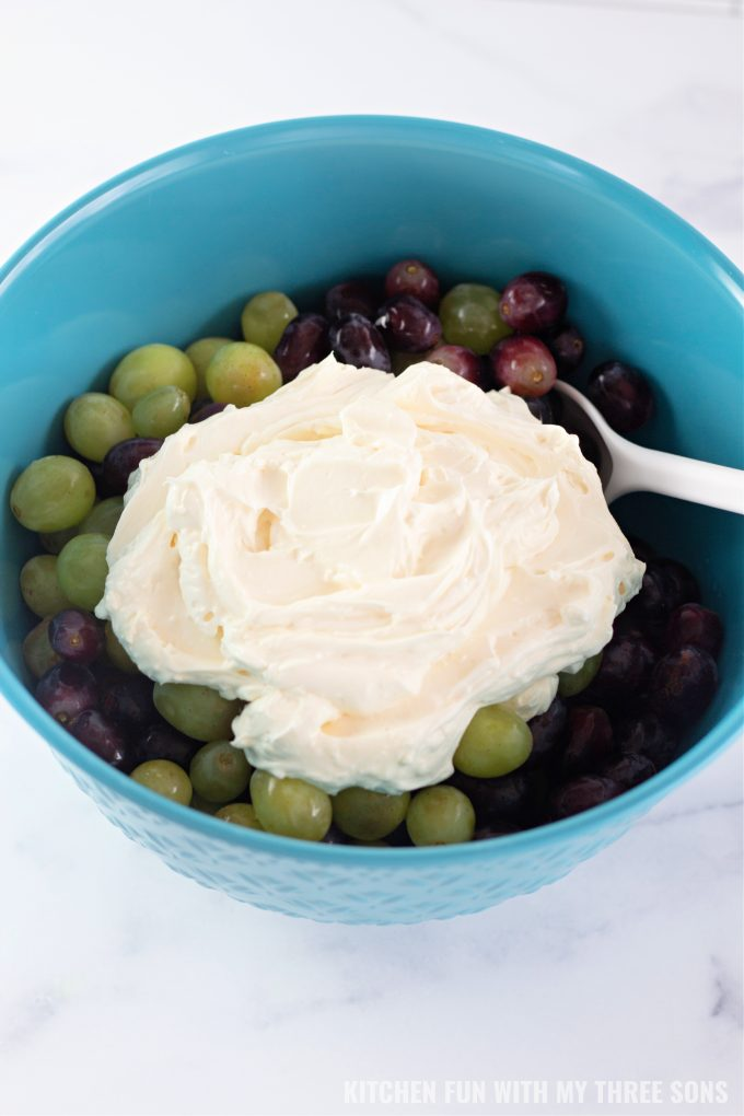 mixing grapes and dressing in a teal mixing bowl.
