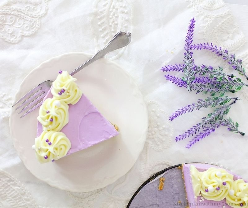 A slice of cheesecake with some lavender flowers.