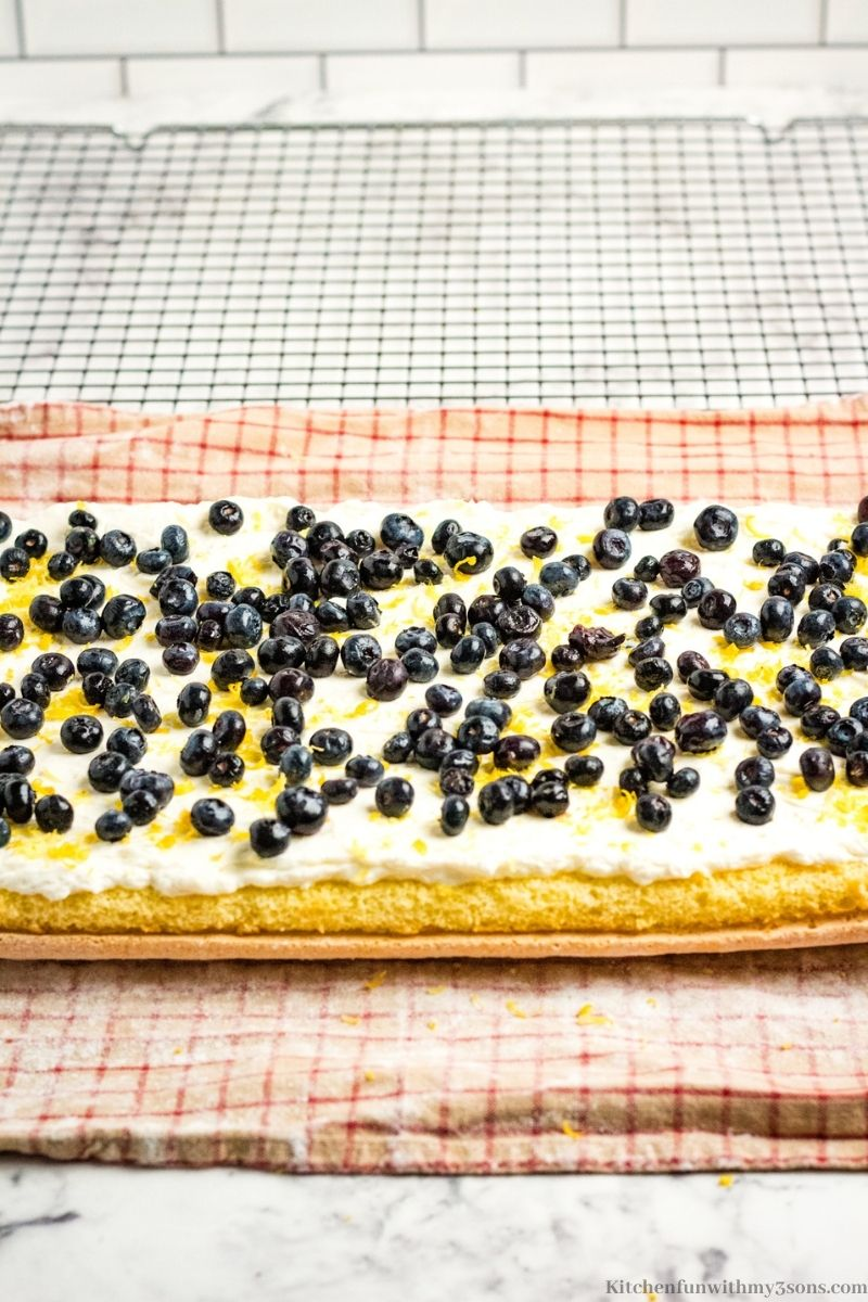 The whipped topping with berries and lemon juice on the sheet cake.