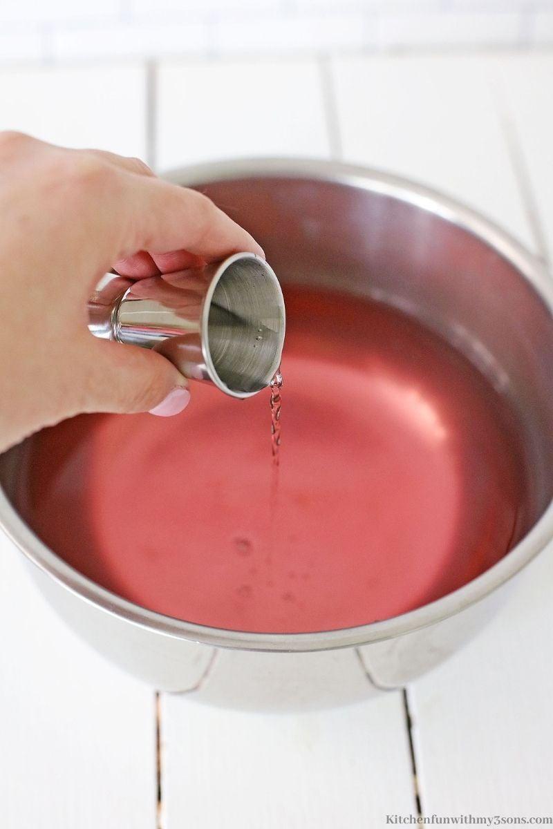 Pouring the vodka into the jello mixture.