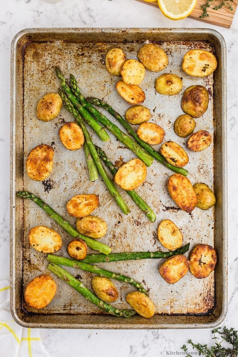 The potatoes and asparagus on a sheet pan.