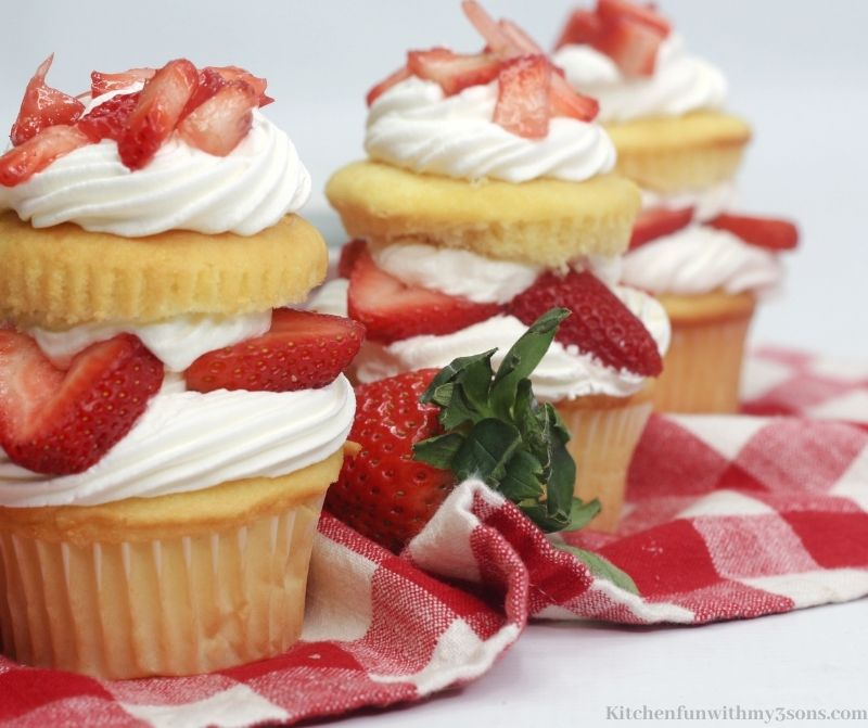 Three of the cupcakes in a diagonal line on a red cloth.