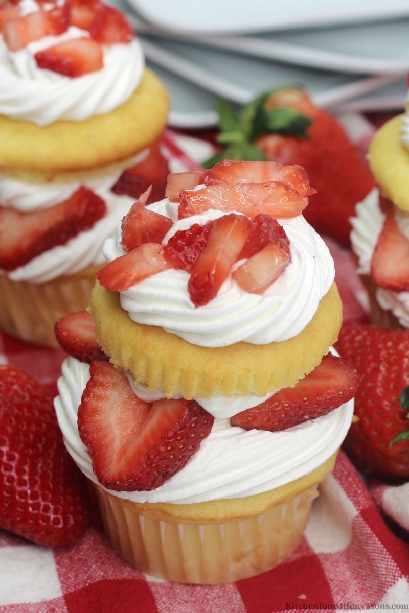 One of the cupcakes with fresh strawberries surrounding it.