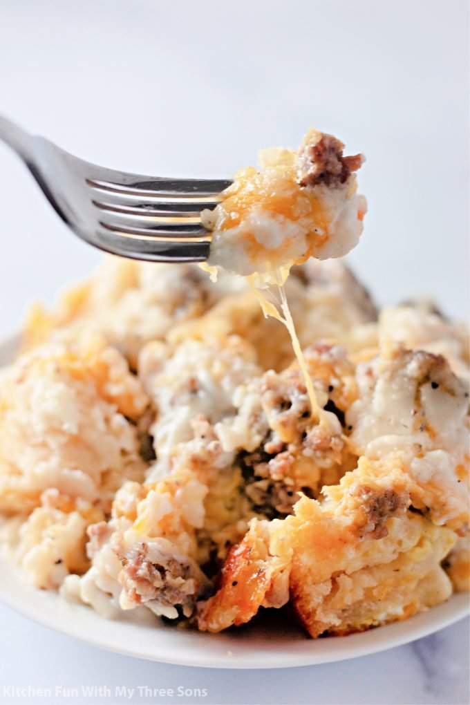 lifting a fork of Biscuits and Gravy Breakfast Casserole.