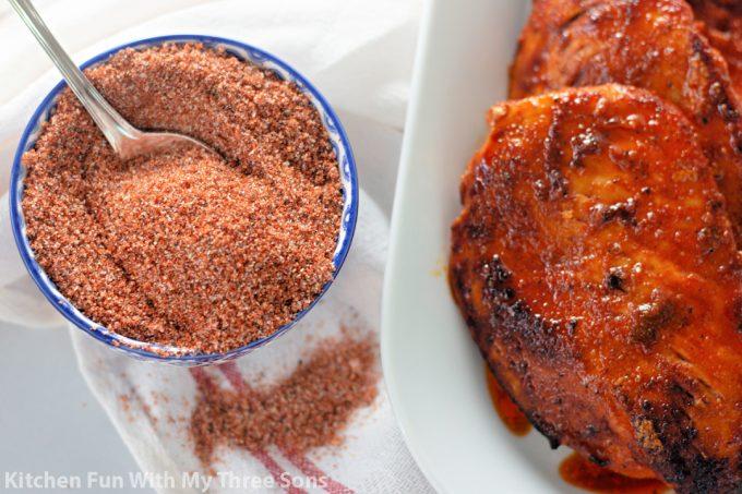 Chicken Spice Rub next to grilled chicken breasts.