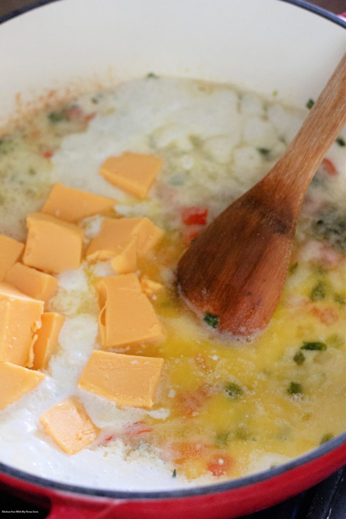 stirring cheese and cream into the pot.