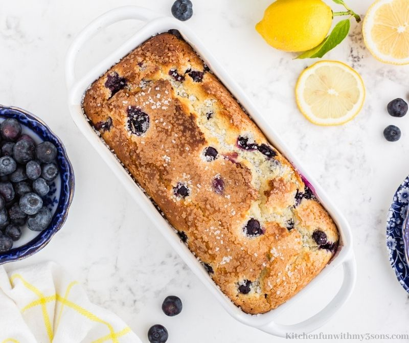 Lemon Blueberry Bread with fresh lemons and blueberries on the side.