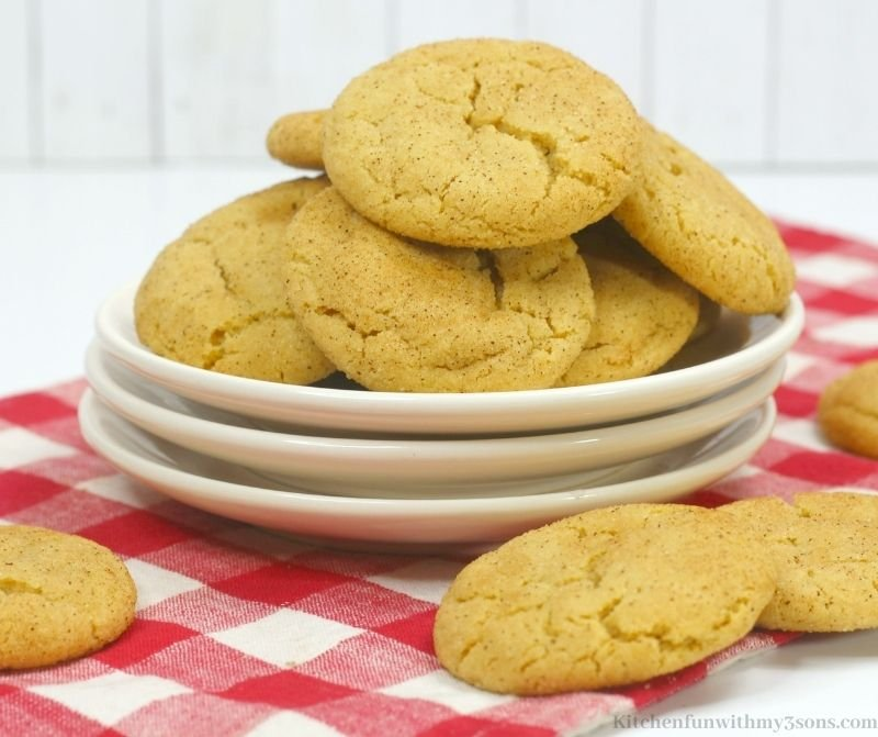The snickerdoodles on a white and red checkered cloth.
