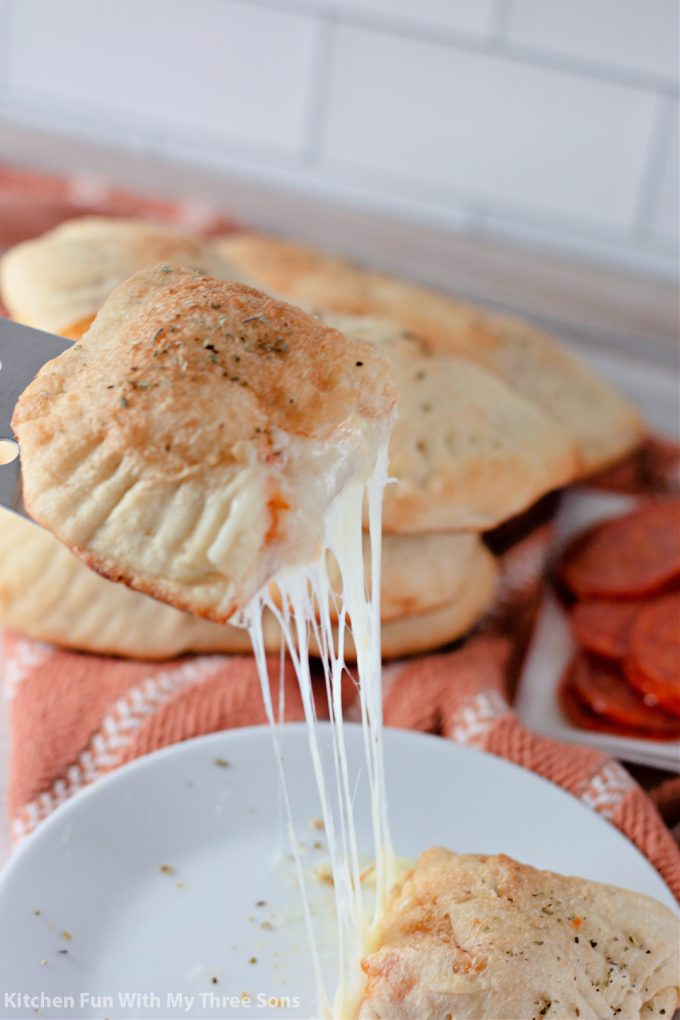 lifting a slice of Pepperoni Pizza Pockets.