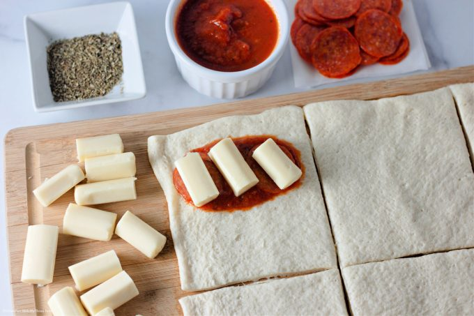 adding sauce and cheese to the pizza crust.