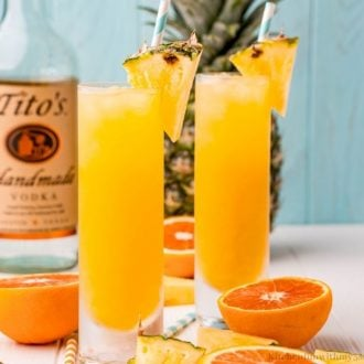 The cocktails with pieces of pineapple on the rims.