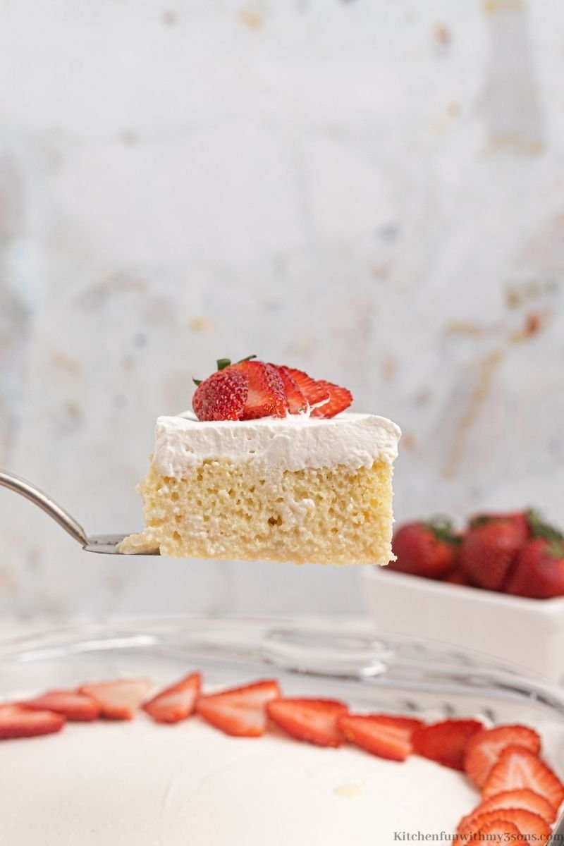 A spatula lifting up a piece of the Tres Leches Cake.