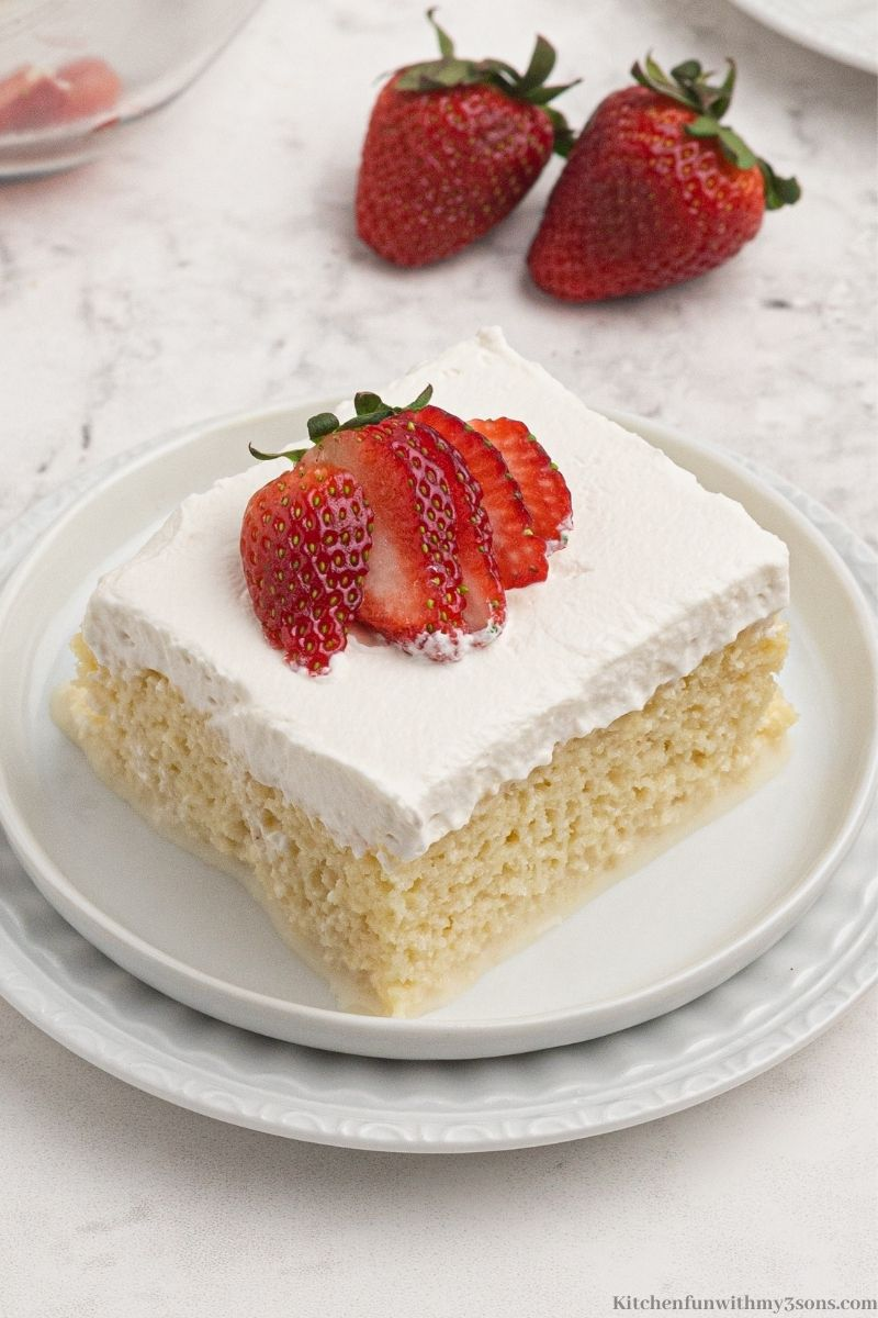 A piece of the Tres Leches Cake with a strawberry on top.