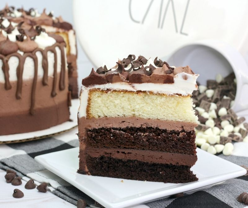 A bowl of chocolate chips spilling behind a piece of cake.