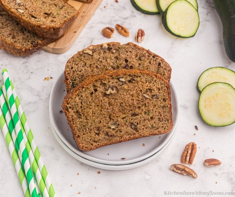 Two slices of zucchini bread on a serving plate.