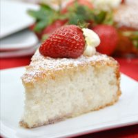 The cake on a white and red checkered cloth.