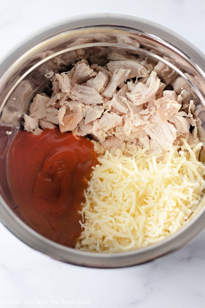 mixing together chicken, cheese, and sauce in a metal bowl.