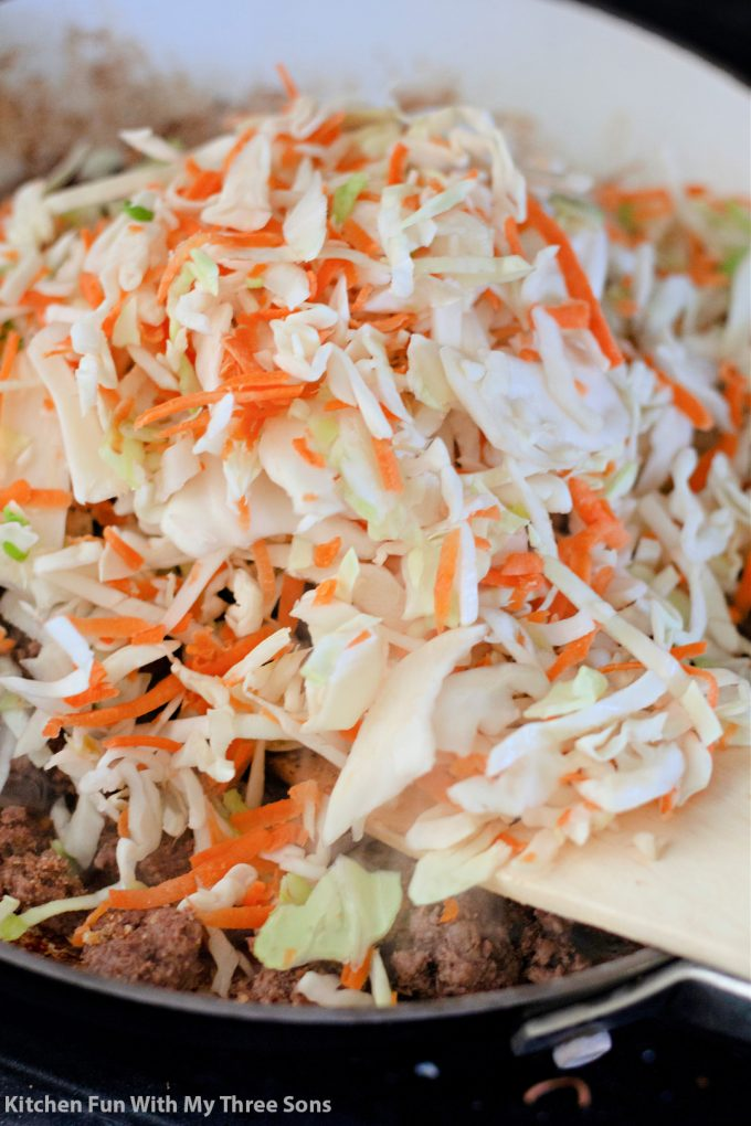 adding the coleslaw mix to the beef in the pan.