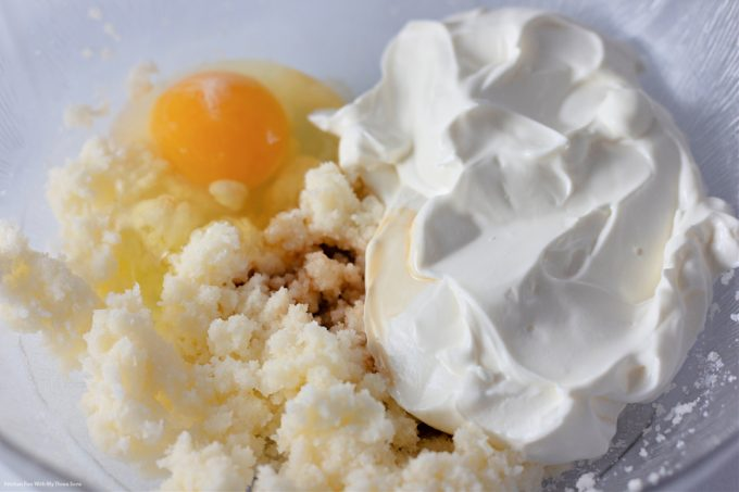 butter, sugar, rum extract, sour cream, and an egg in a clear mixing bowl.