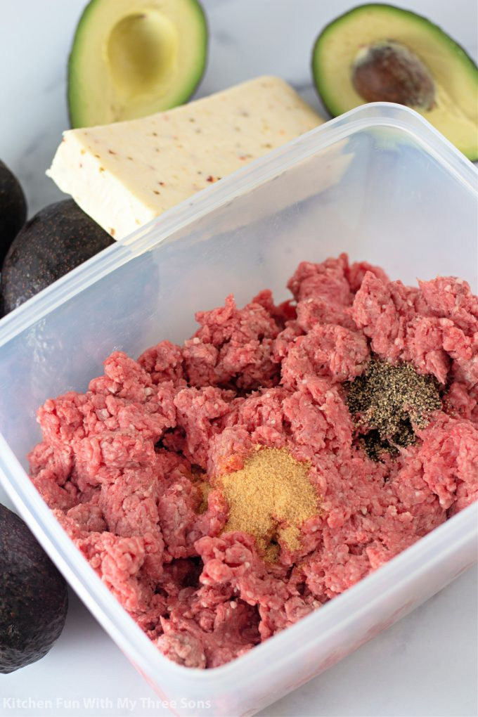 mixing seasoning into the ground beef.