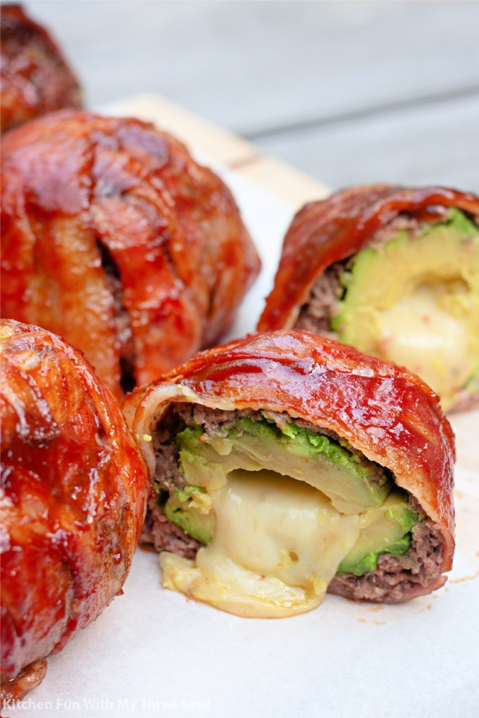 a BBQ Bacon Wrapped Stuffed Avocado sliced open with cheese oozing out.