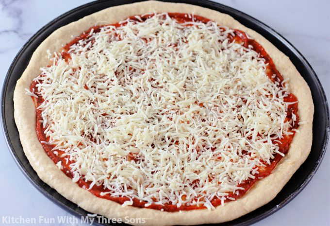 topping the pizza with shredded mozzarella cheese.