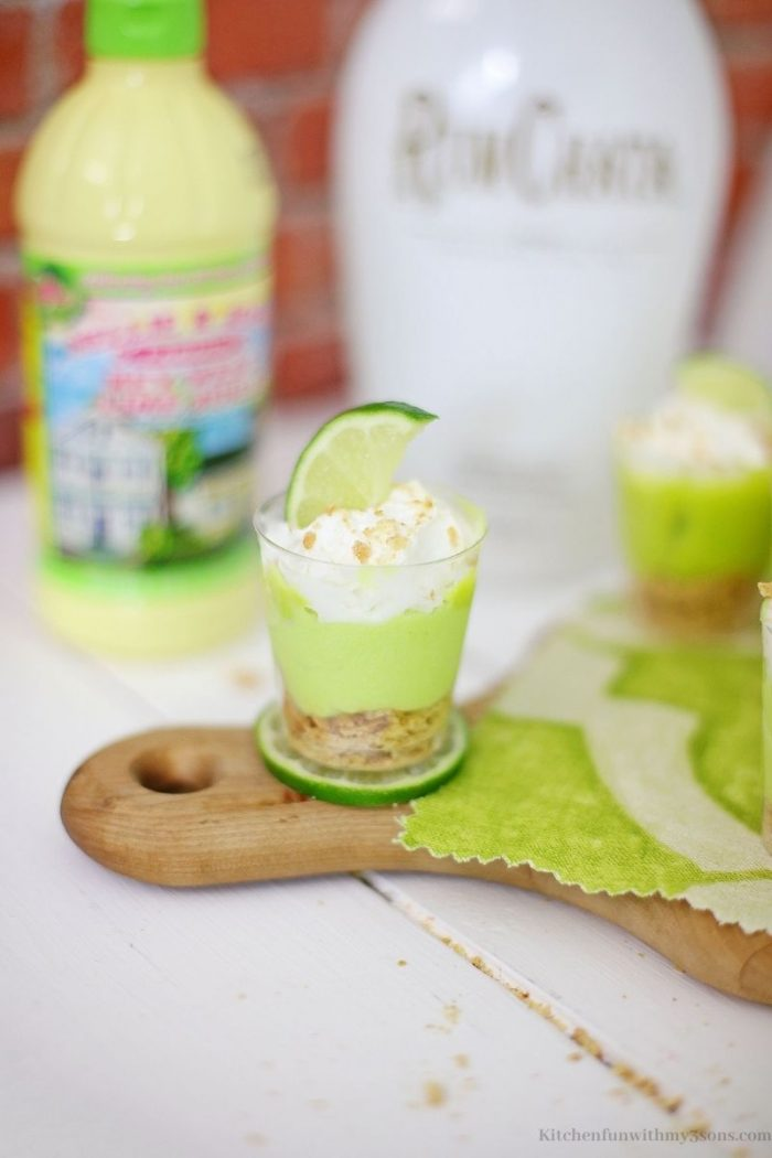 The key lime shooter on the edge of a wooden platter handle.