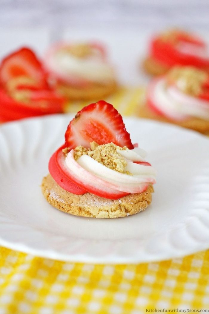 A cookies topped with frosting and a strawberry.