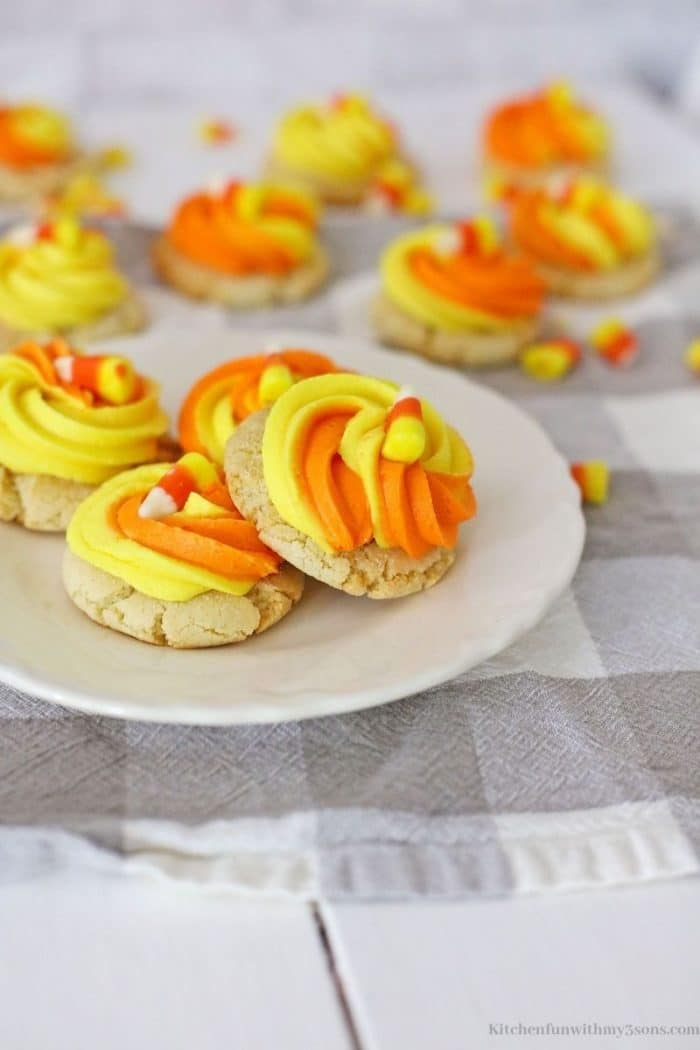 A couple cookies topped with pieces of candy corn.