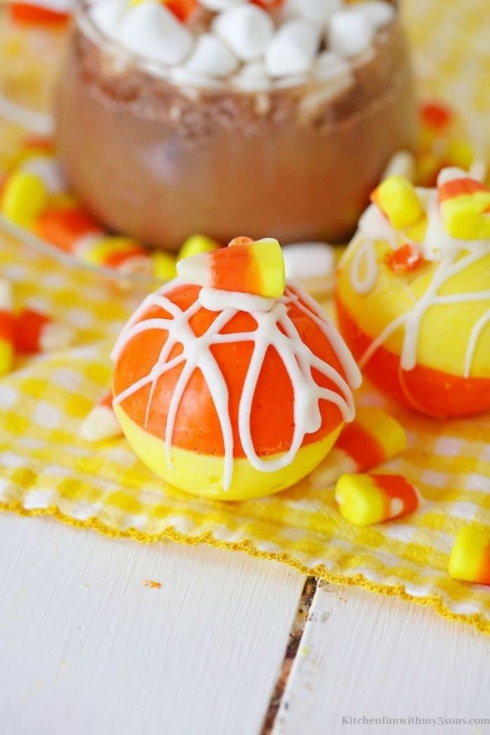 A cocoa bombe surrounded by candy corn.