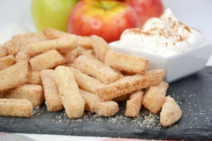 The apple fries with fresh apples behind it.