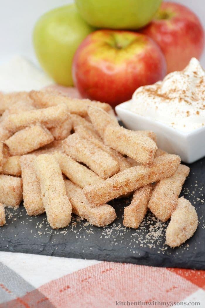 The apple fries on a grey slate.