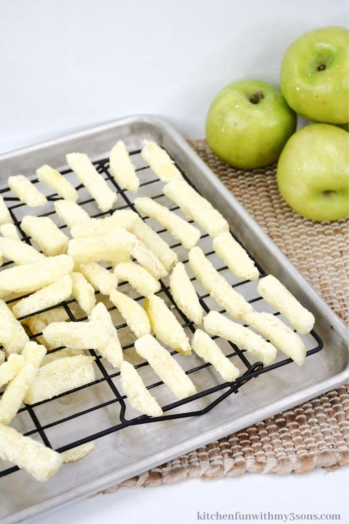 The apple fries on a wire rack.