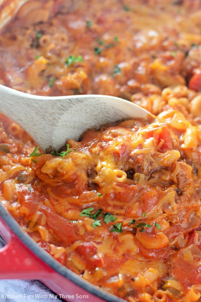 stirring Easy Goulash Recipe with a wooden spoon.