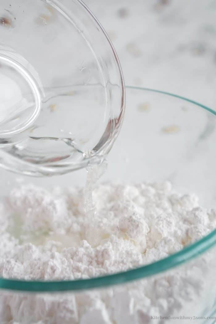 Combining the powdered sugar and water.
