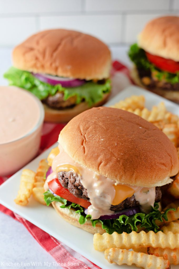 a platter of cheeseburgers topped with homemade burger sauce.
