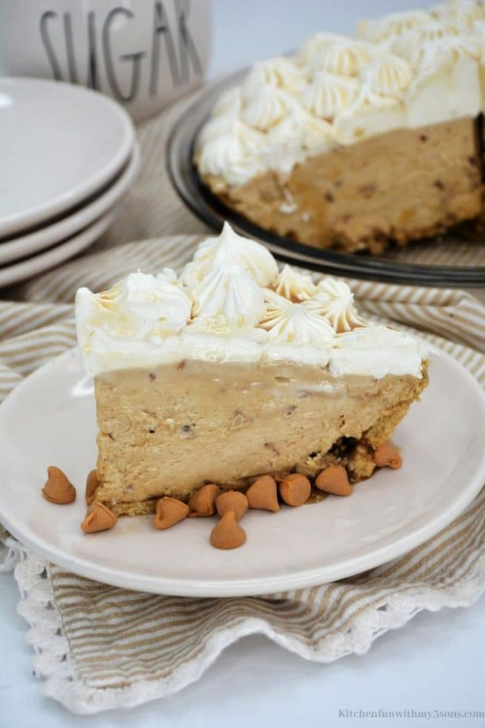 A piece of the pie topped with cream and peanut butter chips.