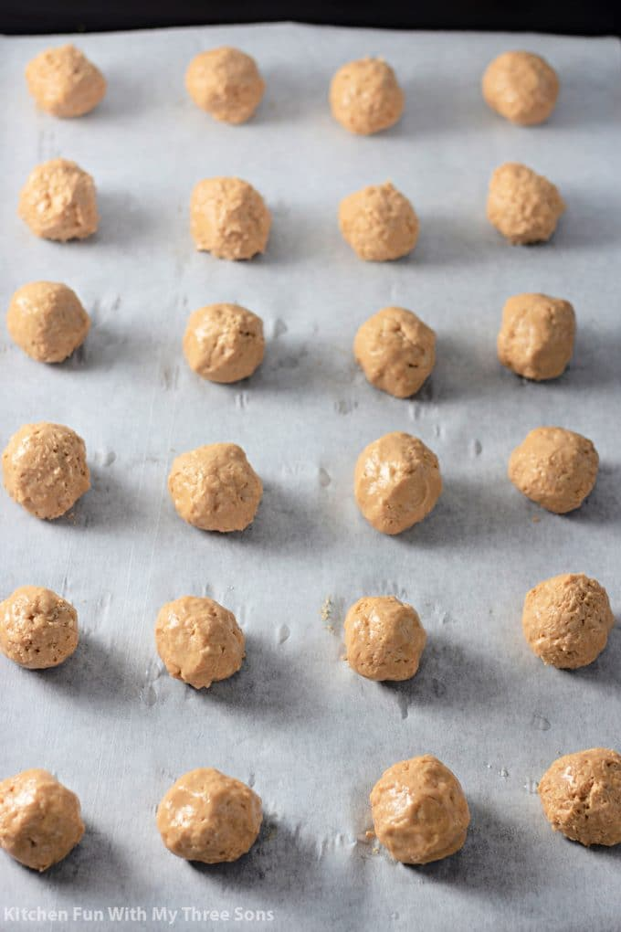 a tray of peanut butter balls on parchment paper.