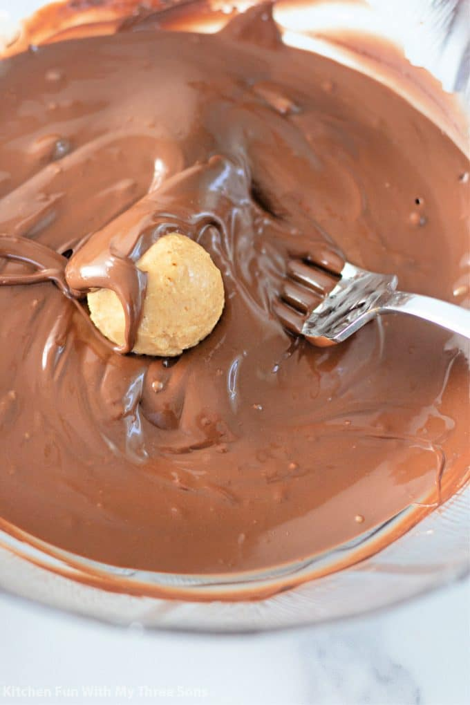 dipping the peanut butter balls into melted chocolate.