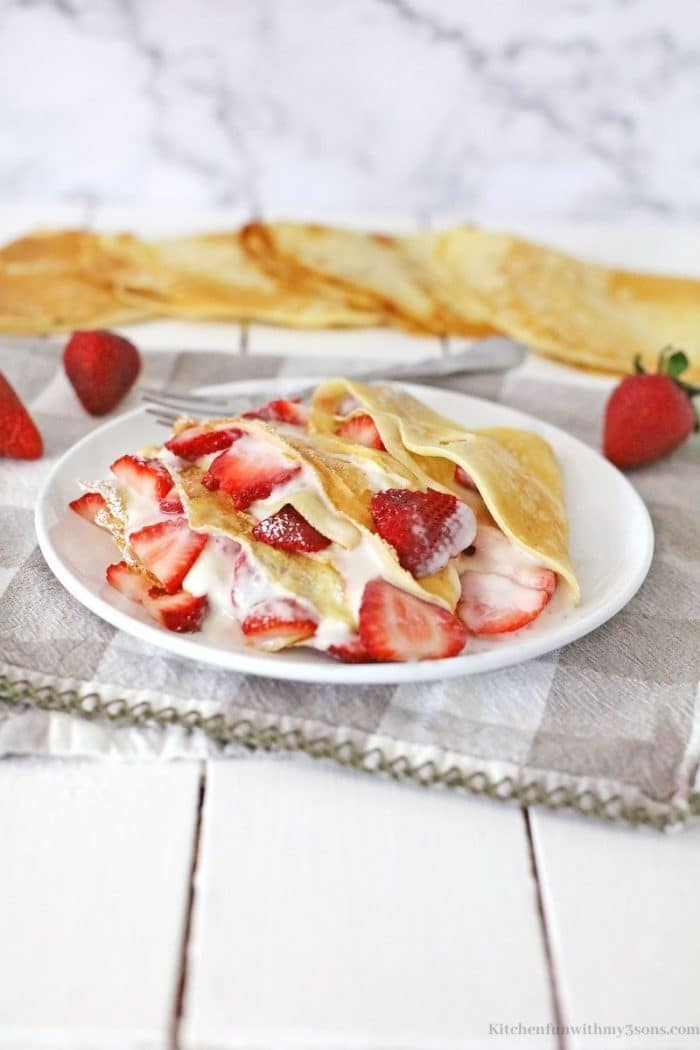 The crepes filled and topped with fresh strawberries.