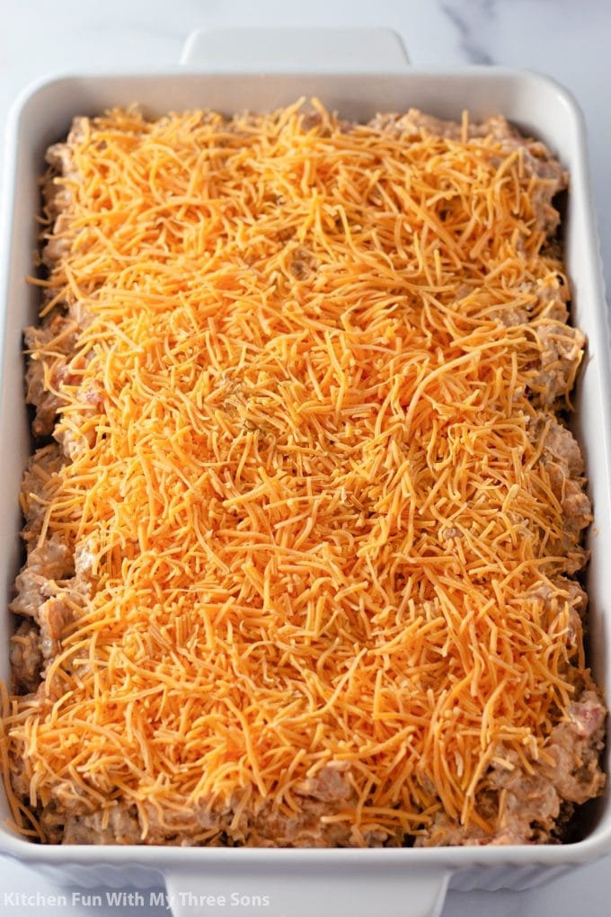 the casserole topped with shredded cheddar cheese.