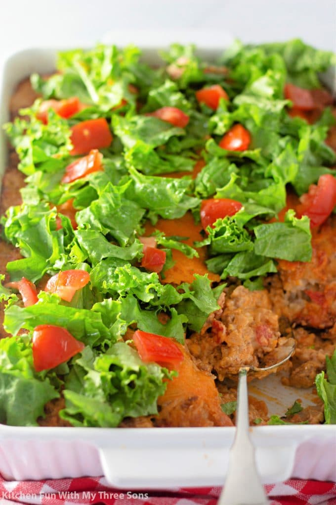 Taco Tater Tot Casserole topped with lettuce and tomato.