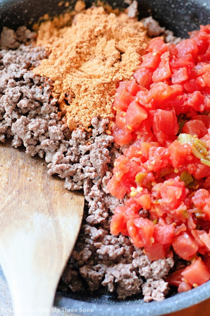 adding the taco seasoning and Rotel to the cooked ground beef.