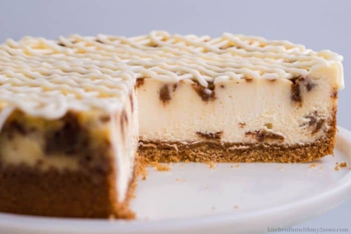 The whole cinnamon roll cheesecake with slices take out.